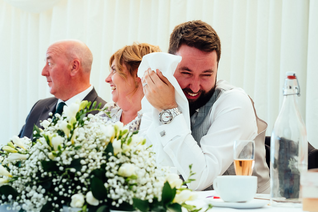 mortified groom hides behind his napkin during his best man speech as his parents look on