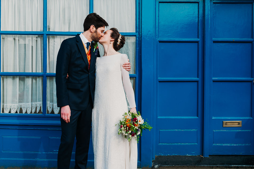 candid london wedding photography couple kiss in front of blue door