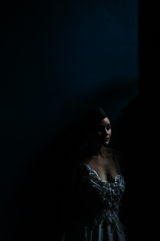 candid moment of bride in the shadows against a blue wall