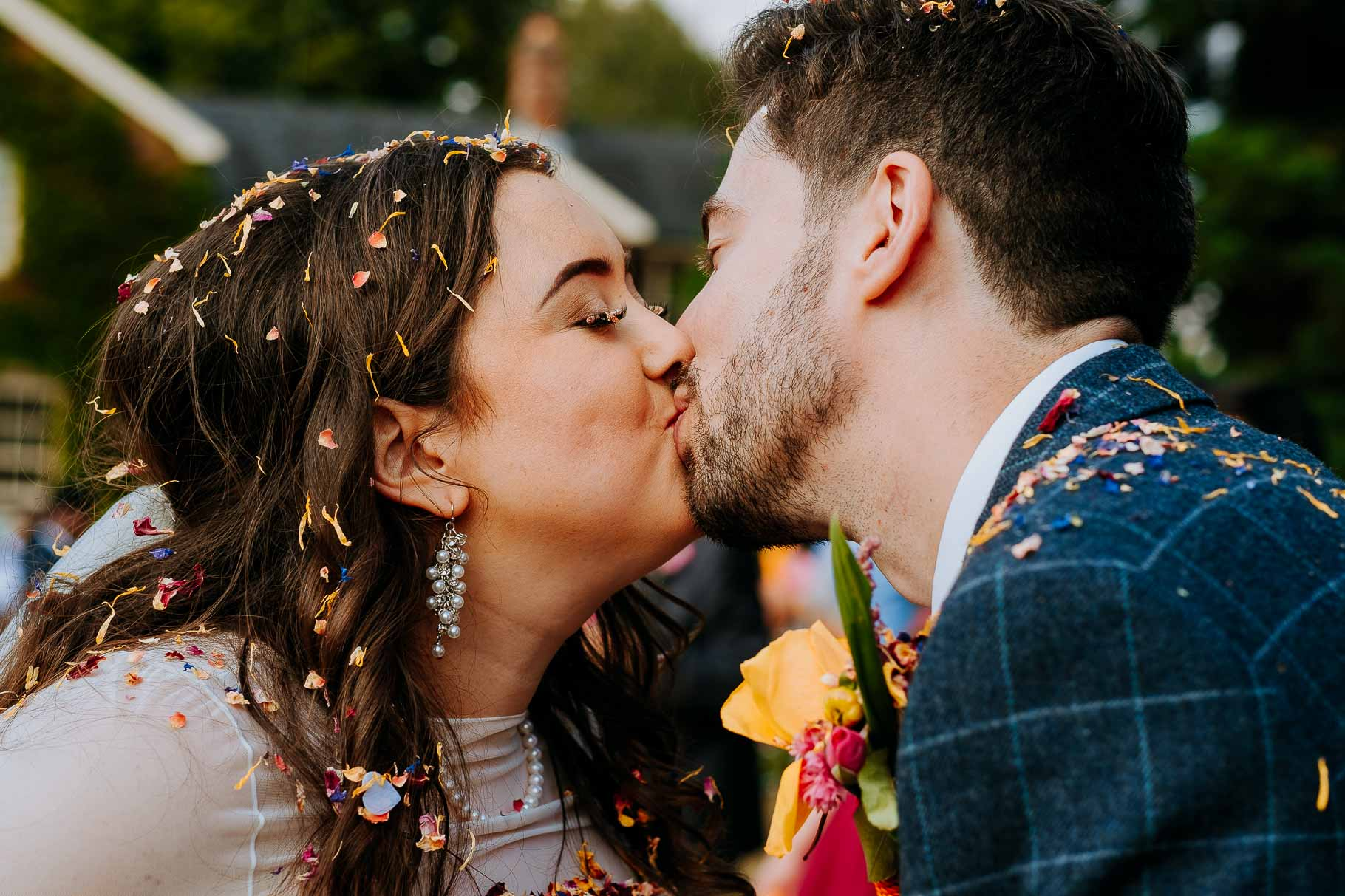 newly married couple kiss covered in colourful confetti