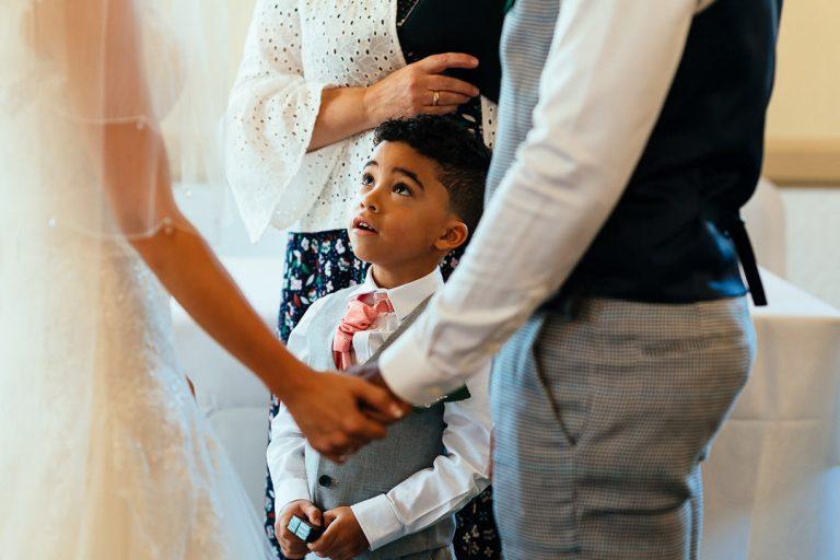 child presents wedding ring at parents service at Glenmore House Surbiton London candid wedding photography