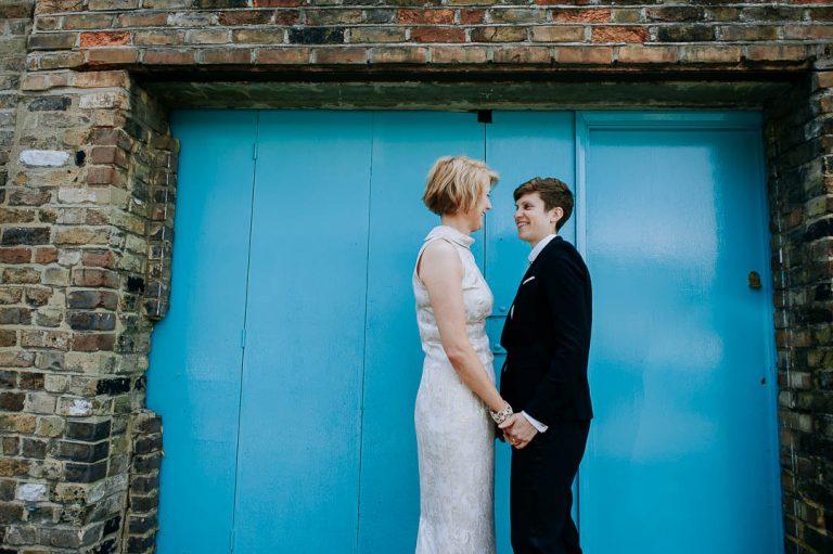 same sex wedding couple outside blue Islington doorway