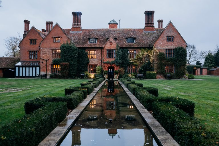 newly married same-sex couple outside woodhall manor wedding venue in Suffolk