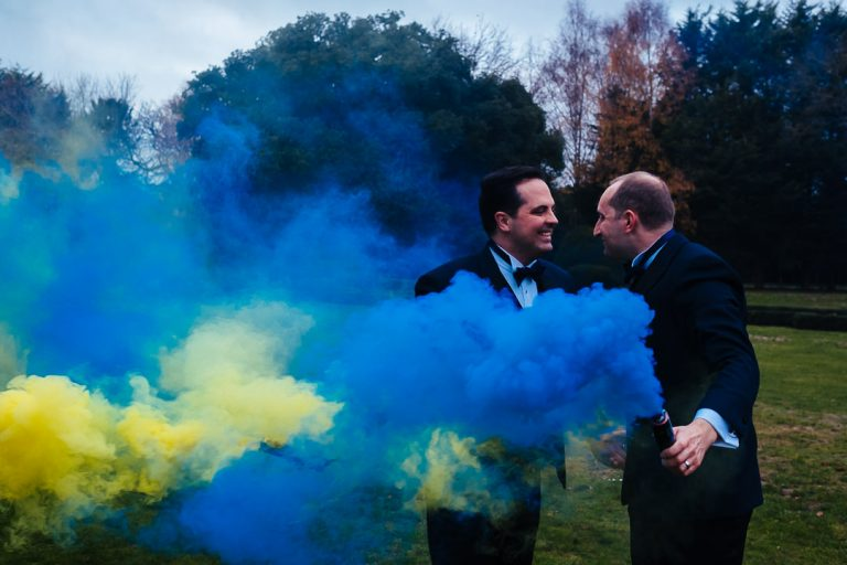 Woodhall manor wedding couple with blue and yellow decorative flares