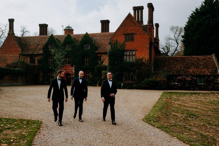 Groom and groomsmen in wedding attire walking outside Woodhall manor Suffolk
