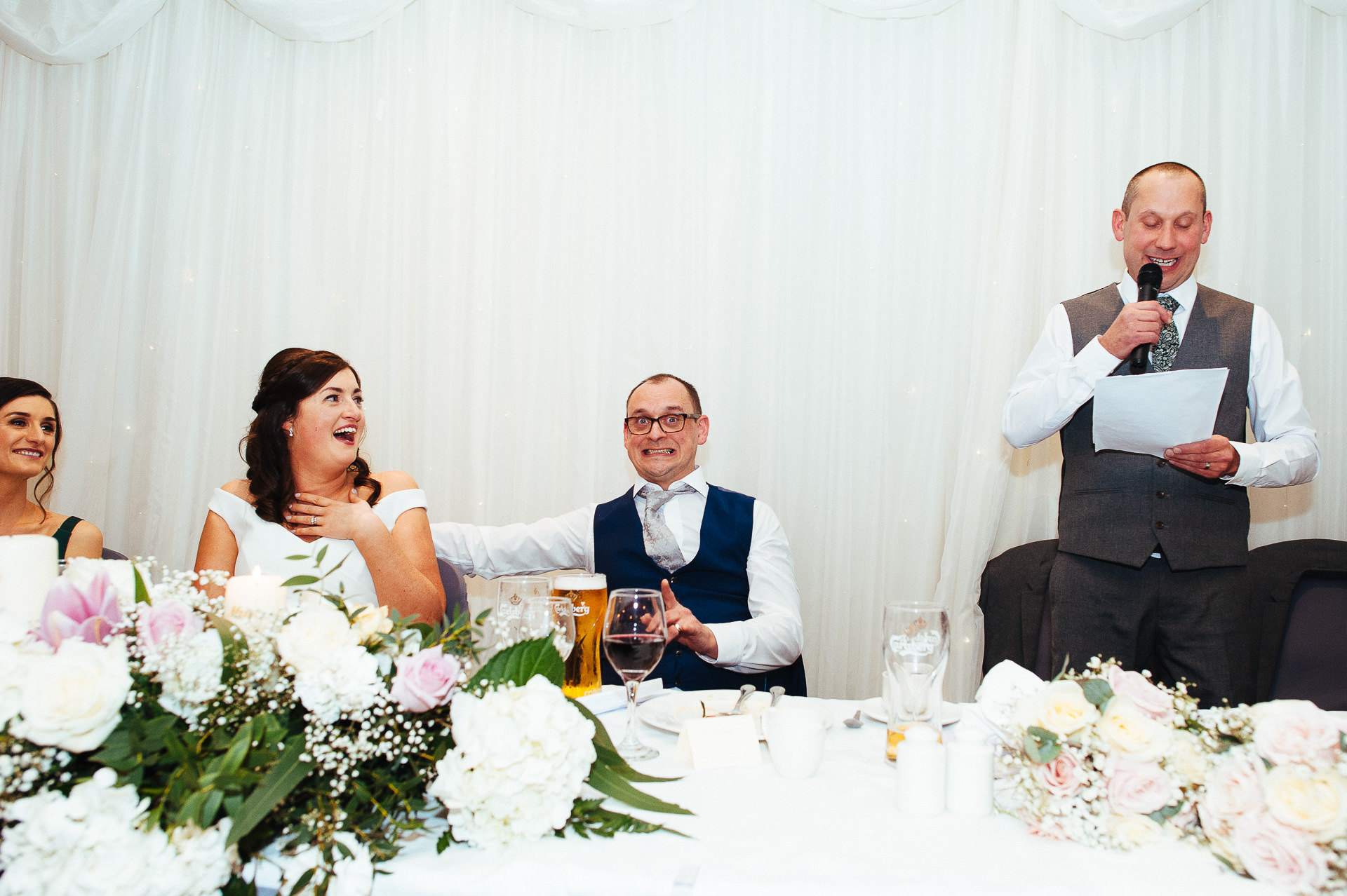 candid moment of best man drinking champagne from the bottle in bright sunshine