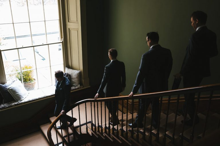 Groom and groomsman descend the stairs at Carton House wedding