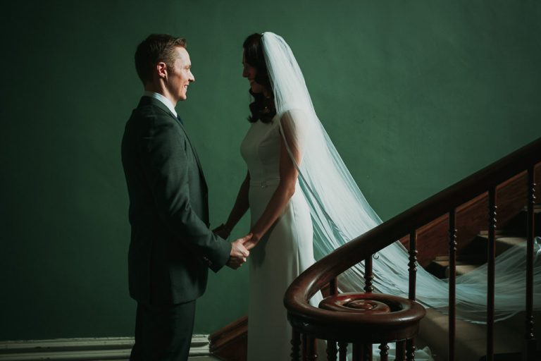 Bride and groom hold hands at Kilshane House against a green wall