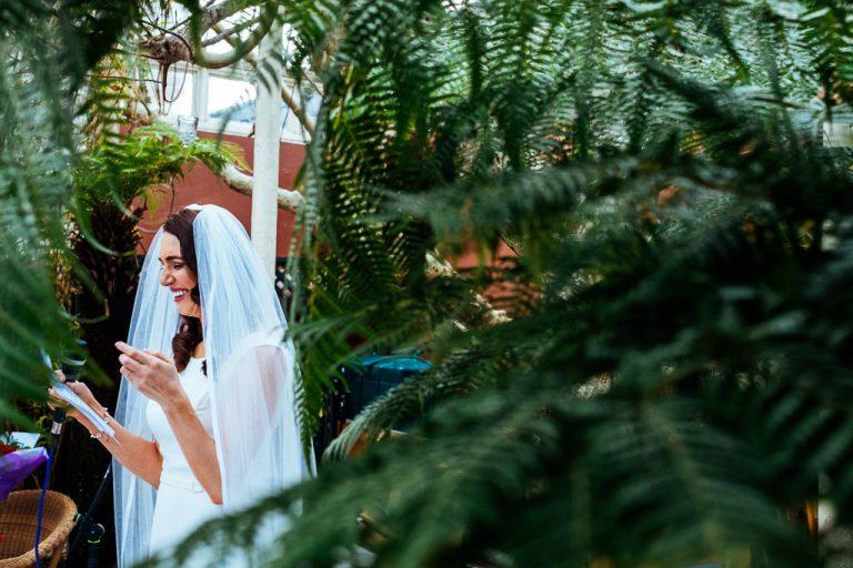 Bride through the ferns at Kilshane House during her wedding speech